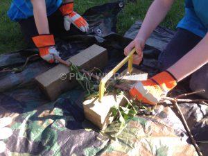 Team work sawing a piece of Elder